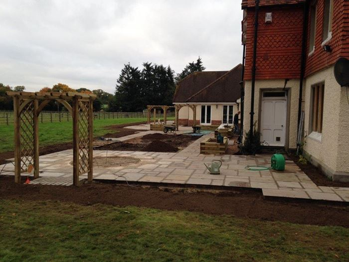 Most of the paving is now laid and reveals the large scale we are working to. The construction of the trellised arches gives this large space definition and shape. The garden also takes shape with the addition of the raised beds made from wooden sleepers – these are proving a popular trend. A circular area can be seen which will be infilled with a concrete base ready for a water feature to be installed at a later date and a large rectangular area of soil in the centre of the paving is made ready for turf to be laid.